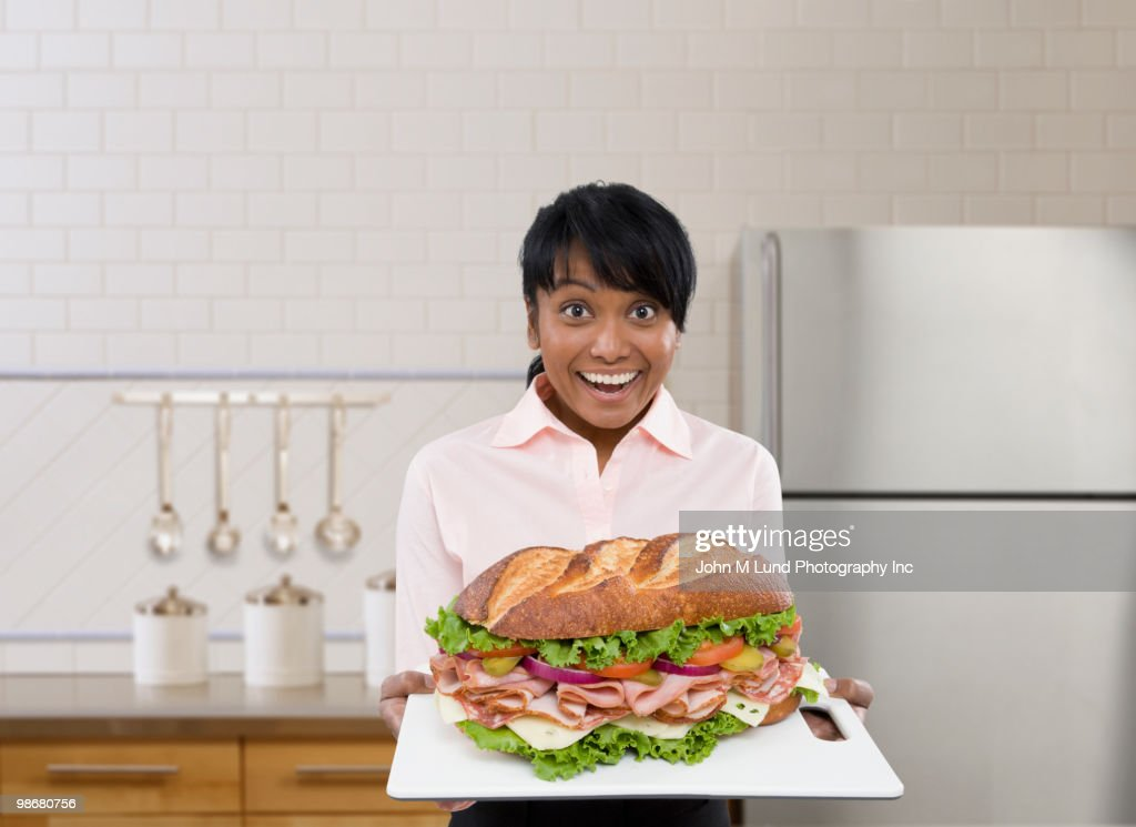 Mixed race woman holding large sandwich on platter : Stock Photo