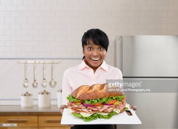 Mixed race woman holding large sandwich on platter