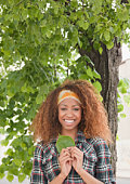 Mixed race woman holding leaf under tree