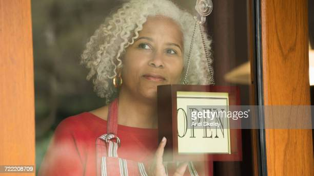 Mixed Race woman holding open sign on door of store