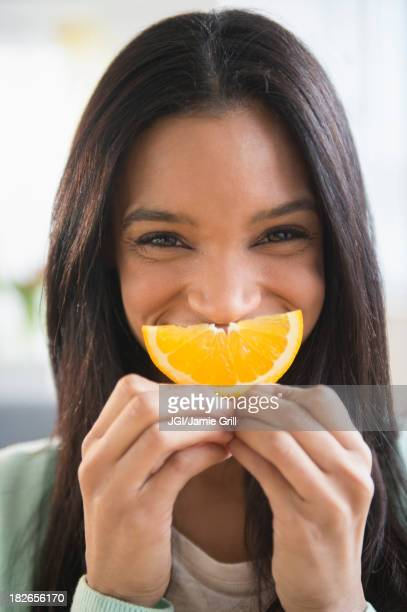 Mixed race woman holding orange slice