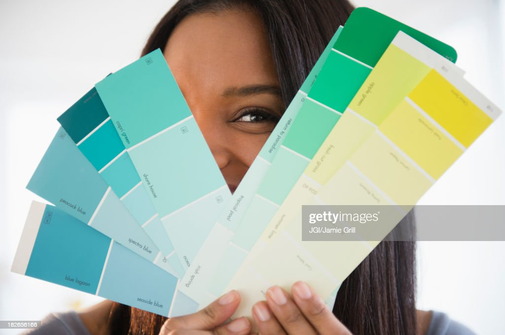 Mixed race woman holding paint swatches : Stock Photo