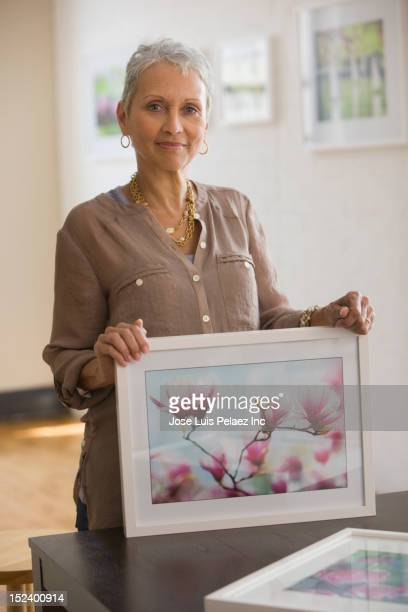 Mixed race woman holding picture of flowers