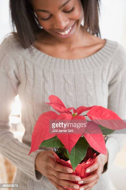 Mixed race woman holding poinsettia plant