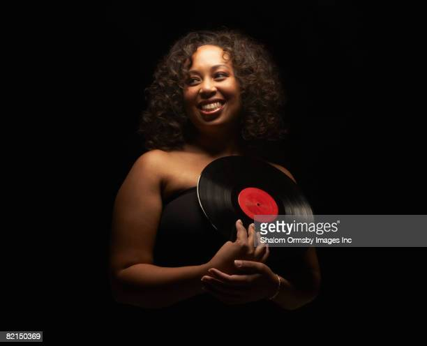 Mixed Race woman holding record album