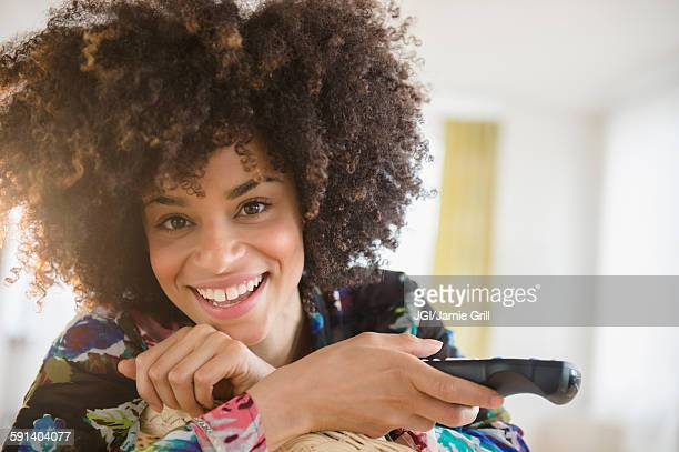 Mixed race woman holding television remote control