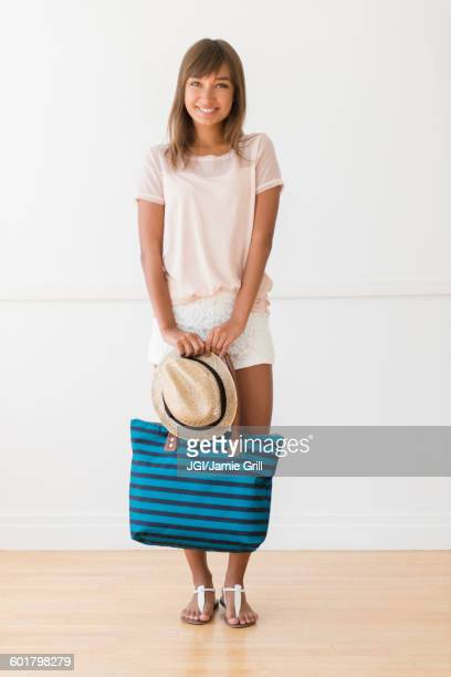 Mixed race woman holding tote bag