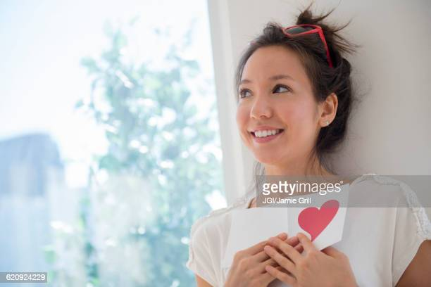 Mixed race woman holding Valentine card