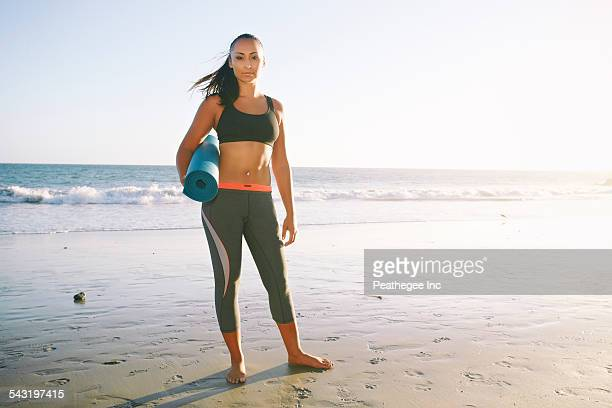 Mixed race woman holding yoga mat on beach