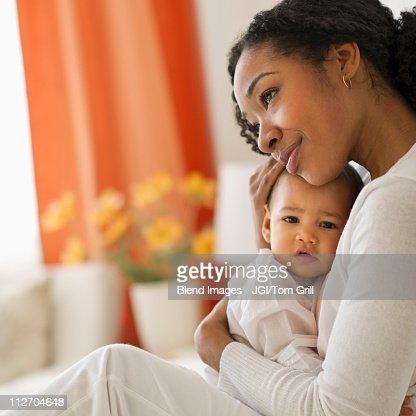 Mixed race woman hugging baby : Bildbanksbilder