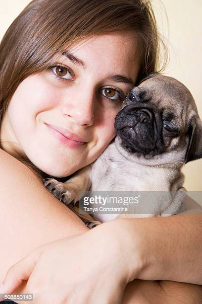 Mixed race woman hugging pug