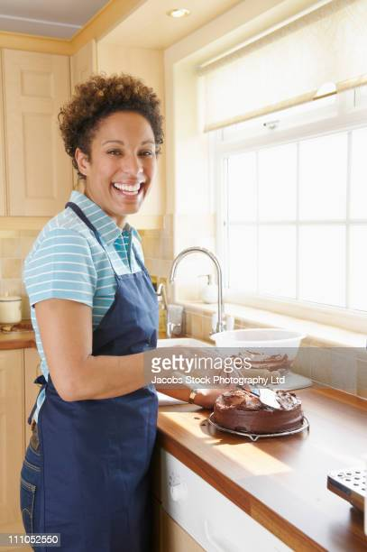 Mixed race woman icing cake