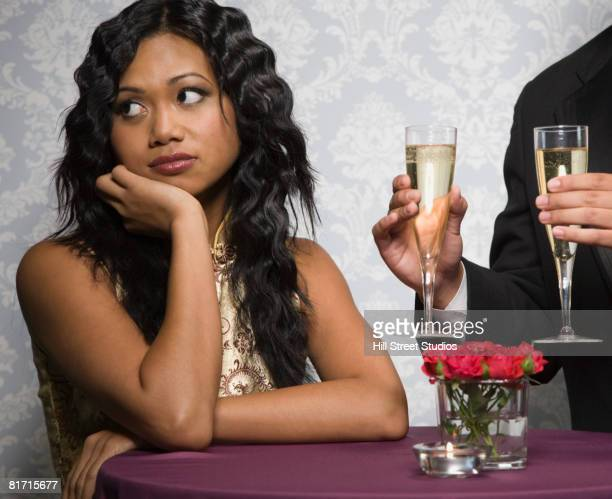 Mixed Race woman ignoring man holding champagne