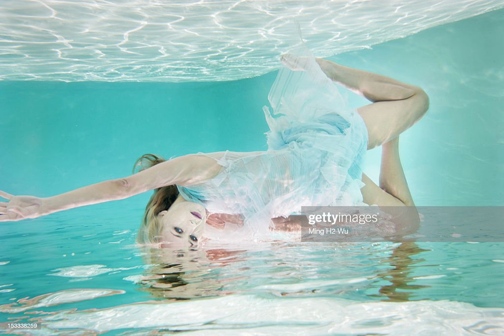 Mixed race woman in dress underwater in swimming pool : Stock Photo