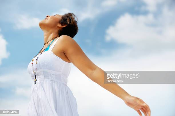 Mixed race woman in sundress against cloudy sky