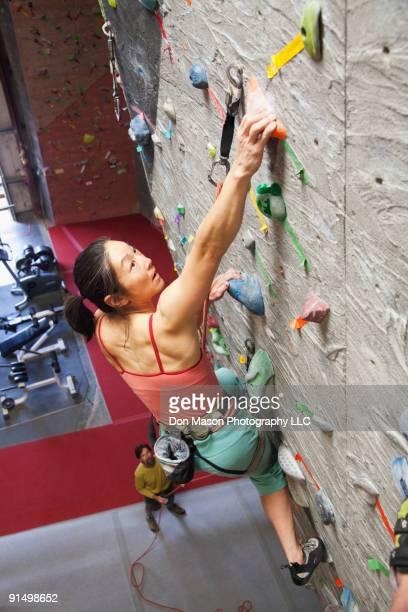 Mixed race woman indoor rock climbing