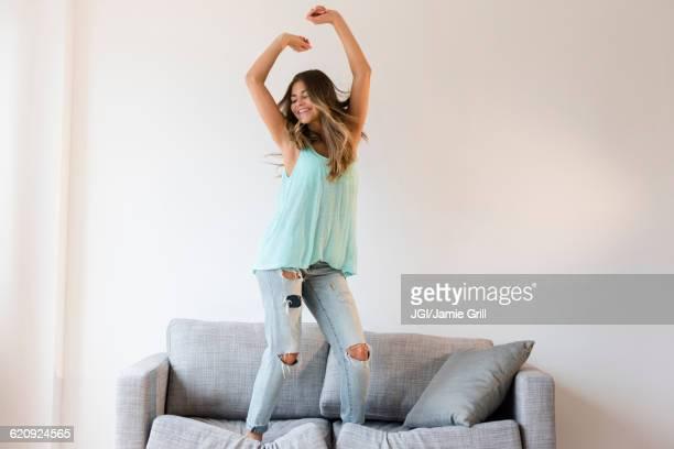 Mixed race woman jumping on sofa