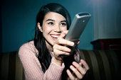 Mixed race woman laughing at TV
