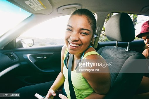 Mixed Race woman laughing in car