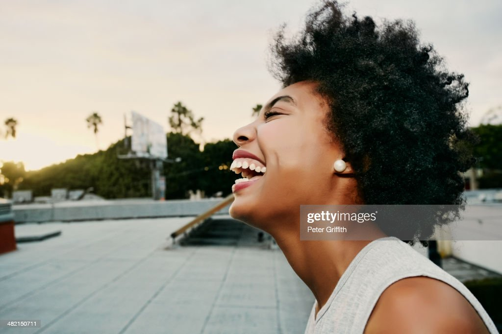 Mixed race woman laughing on urban rooftop : Stock Photo