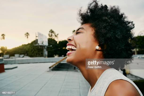 Mixed race woman laughing on urban rooftop