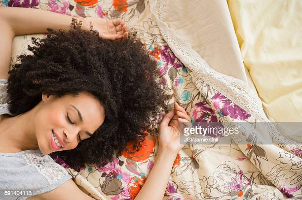 Mixed race woman laying on bed