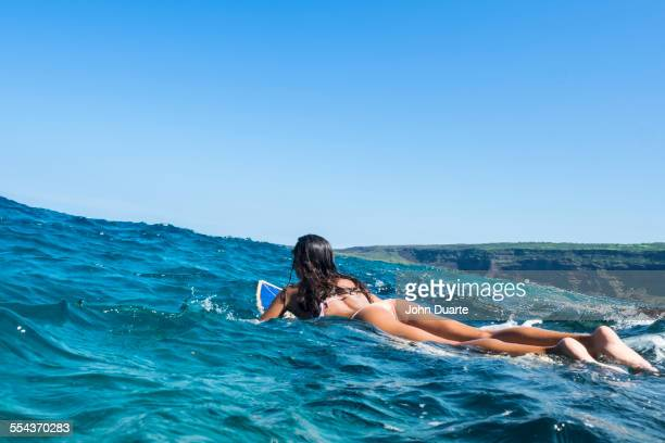 Mixed race woman laying on surfboard in ocean waves
