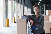 Mixed race woman leaning on box at warehouse loading dock
