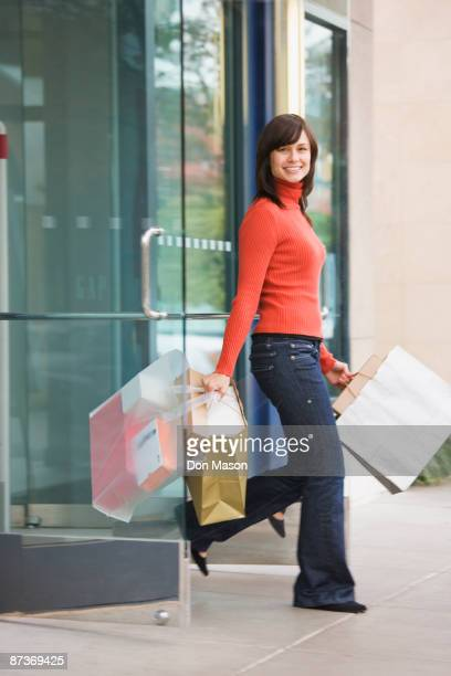 Mixed race woman leaving store with shopping bags