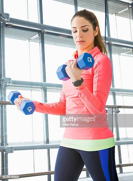 Mixed race woman lifting weights in gym