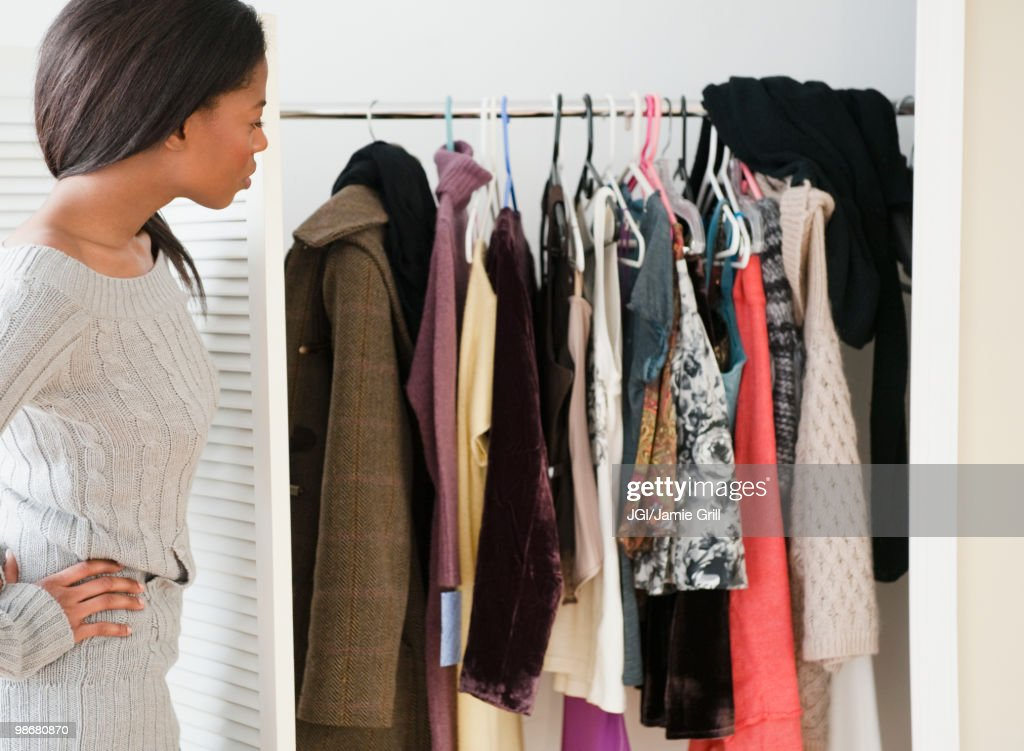 Mixed race woman looking at clothes in closet