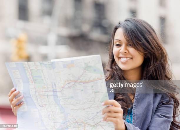 Mixed Race woman looking at map