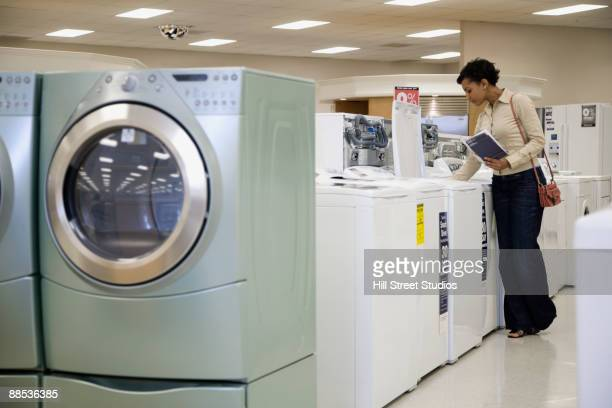 Mixed race woman looking at washing machines in showroom