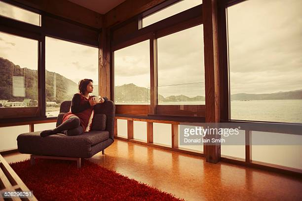 Mixed race woman looking out window of modern house