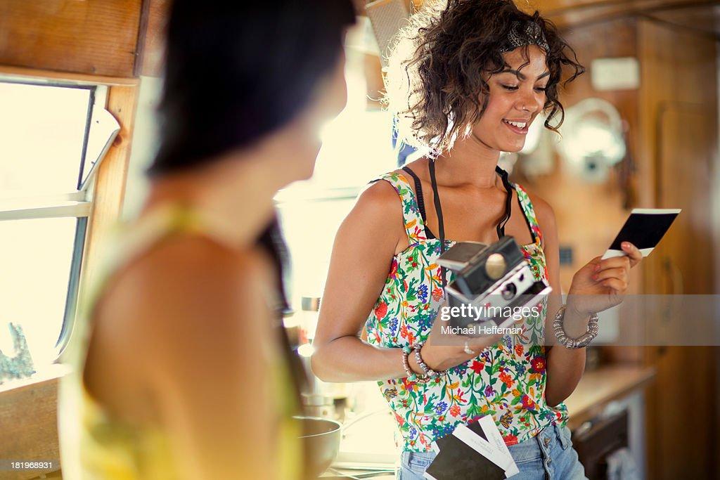 mixed race woman looks at polaroid