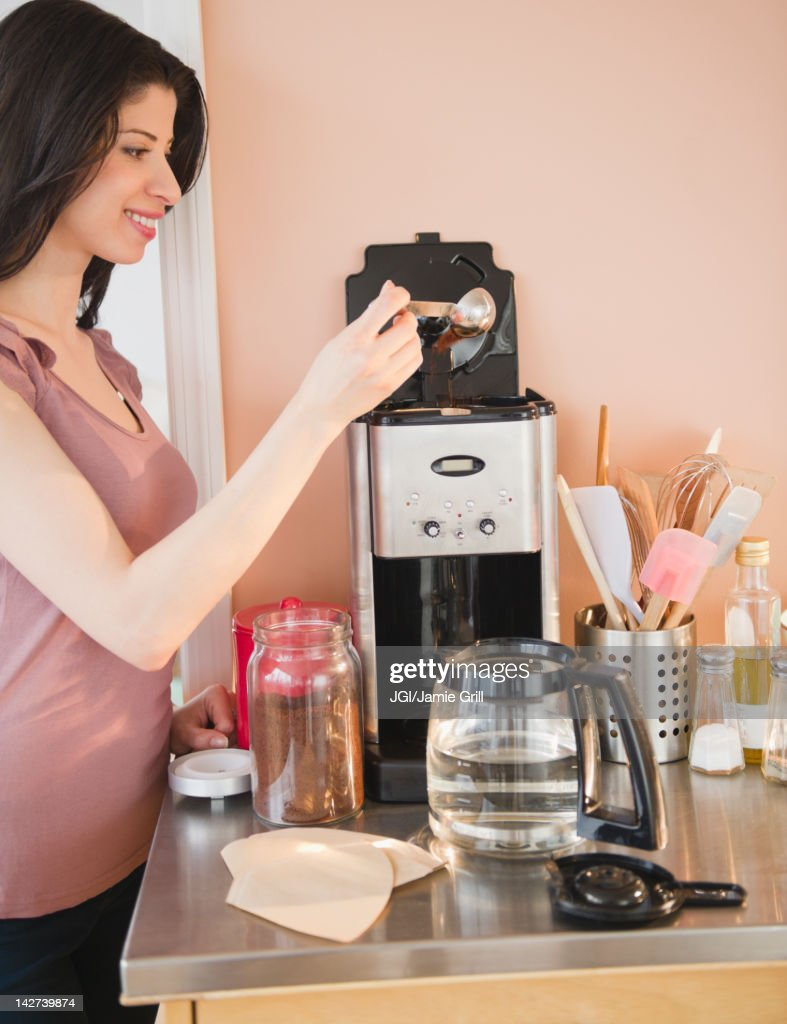 Mixed race woman making coffee
