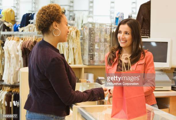 Mixed Race woman making purchase at boutique