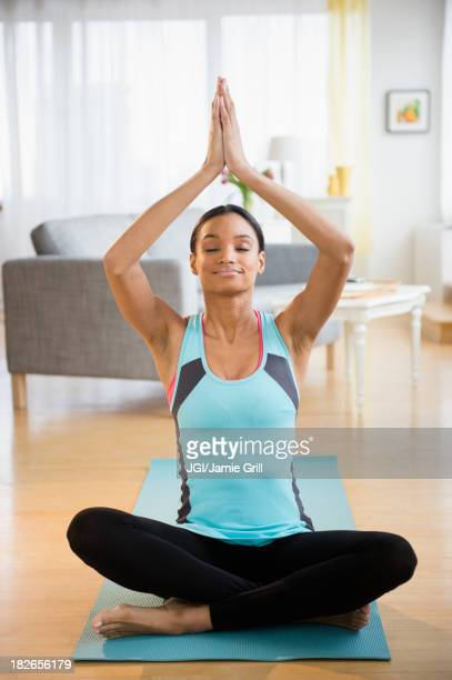 Mixed race woman meditating in living room