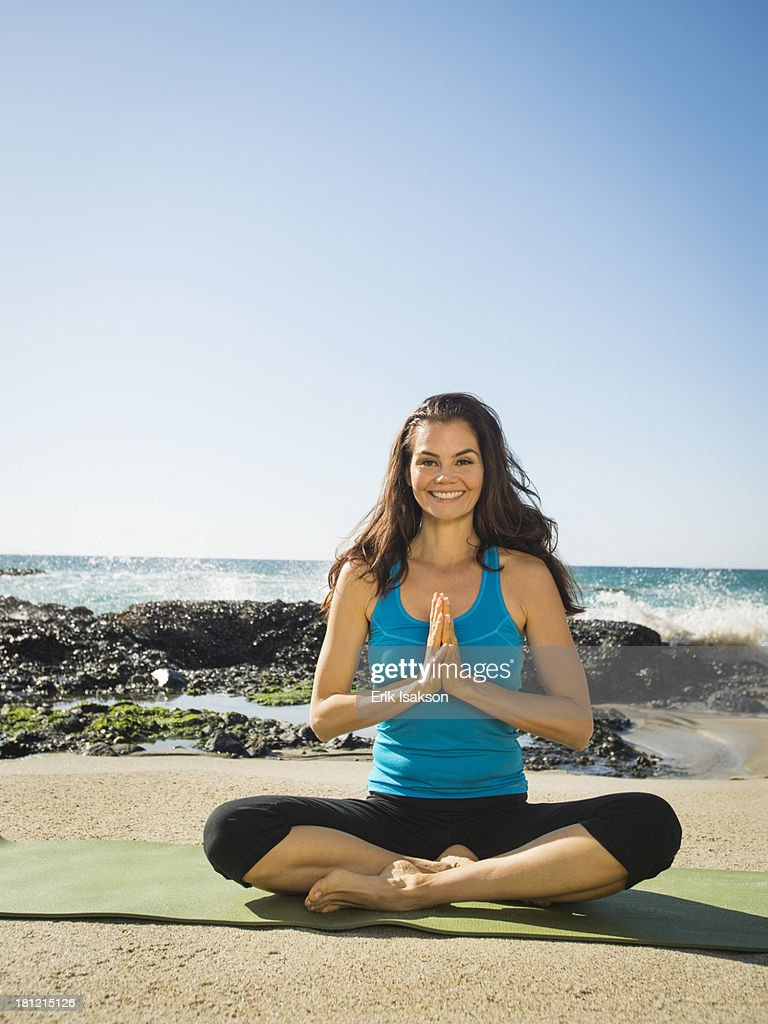 Mixed race woman meditating on beach : Stock Photo