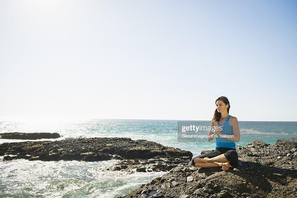 Mixed race woman meditating on rocky beach : Stock Photo