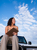 Mixed Race woman on truck holding clipboard