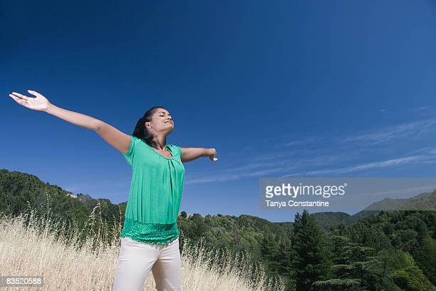Mixed race woman outdoors with arms outstretched