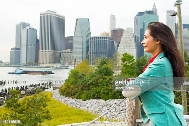 Mixed race woman overlooking park and river, New York, New York, United States