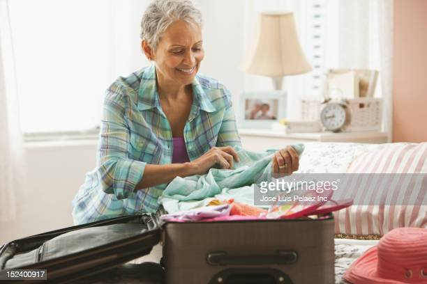 Mixed race woman packing suitcase