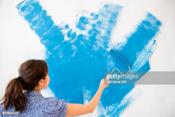 Mixed race woman painting wall