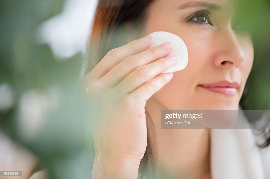 Mixed race woman patting makeup on face : Stock-Foto