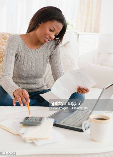 Mixed race woman paying bills in living room