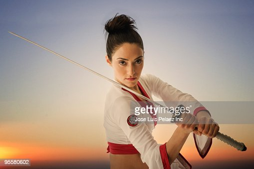 Mixed race woman performing martial arts with sword : Stock Photo