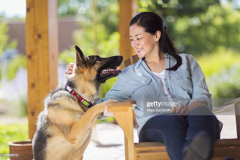 Mixed race woman petting dog : Stock Photo