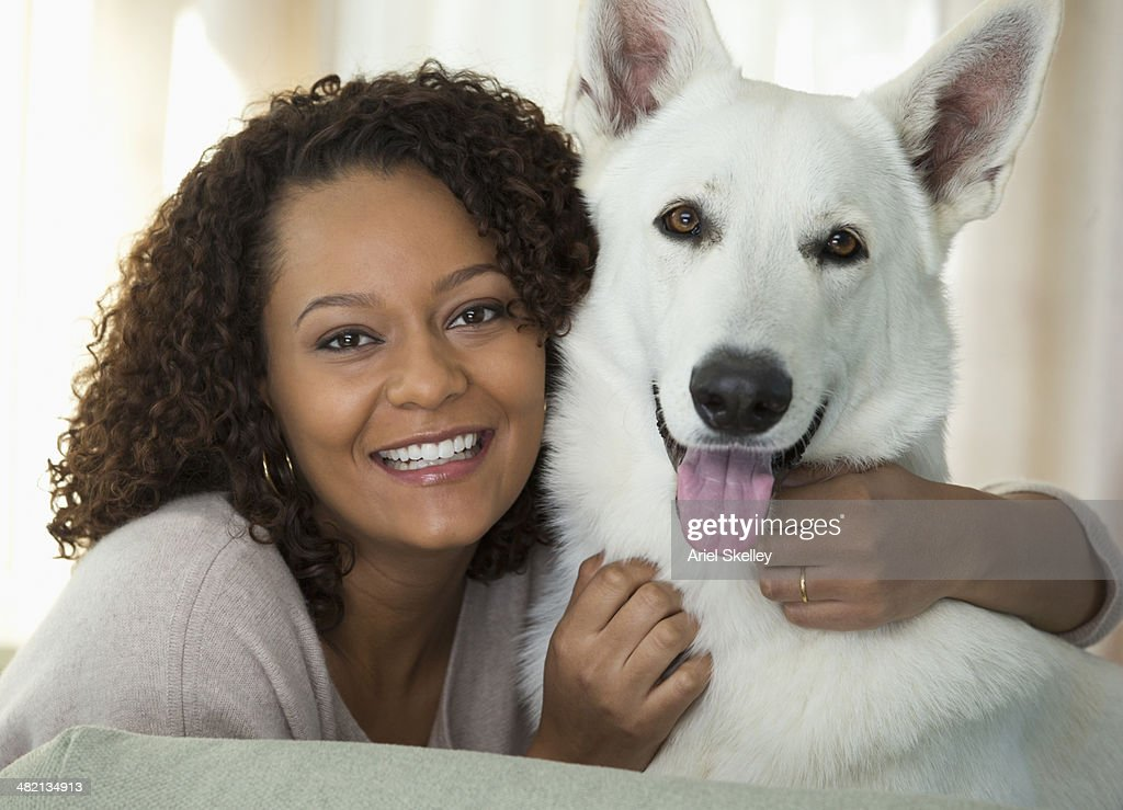 Mixed race woman petting dog